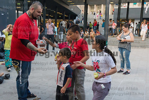 Migration aid volunteer distributes food to illegal migrants in a public underpass designated as a transit zone at Eastern railway station in downtown Budapest, Hungary on August 13, 2015. ATTILA VOLGYI