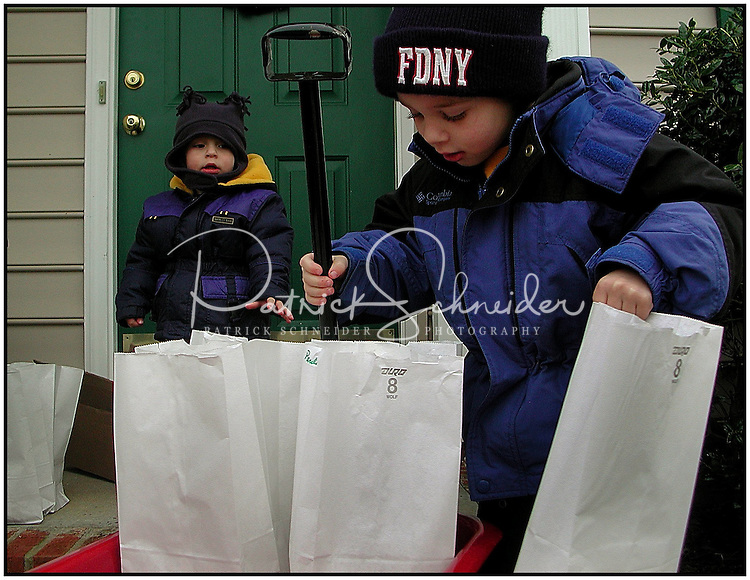 "A family prepares to set out luminaries. Photo taken near Charlotte, NC. Model released image. ""FDNY"" can be removed from hat if used for illustration."