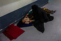 LASHKAR GAH, AFGHANISTAN - SEPTEMBER 24: A woman sits on the floor of a corridor with her two children, waiting for her son to be seen and registered in to the ITFC (Inpatient Therapeutic Feeding Centre) ward at the Bost Hospital, a Medecins Sans Frontiers (MSF) assisted hospital, on September 24, 2013 in Lashkar Gah, in Helmand Province, Afghanistan.