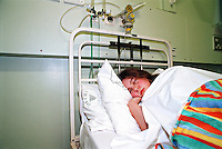 Teenager confined to bed in the peadiatric ward of a hospital.