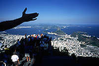 A tourist mimics Rio de Janeiro's famous statue of Christ the Redeemer atop Corcovado mountain, as fellow gazers take in the view of the city and its promontory Sugarlof mountain.