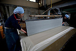 Artisans make washi paper at Iwano Heizaburo Seijijo in Echizen, Fukui Prefecture, Japan on 21 Feb. 2013. Photographer: Robert Gilhooly  .Artisans guide a freshly made sheet of washi paper onto spotless sheets that will be taken to drying rooms at Iwano Heizaburo Seijijo in Echizen, Fukui Prefecture, Japan on 21 Feb. 2013. Photographer: Robert Gilhooly  .