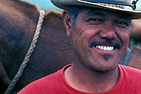 Portrait of a smiling paniolo (cowboy) in front of his horse