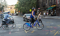 A bicycle enthusiast uses her Citibike to cross Greenwich Avenue in the Greenwich Village neighborhood of New York on Tuesday, August 4, 2015.  (© Richard B. Levine)