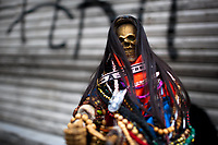 A figurine of Santa Muerte (Saint Death)  is seen placed on the street during a religious pilgrimage in Tepito, a dangerous district of Mexico City, Mexico, 1 June 2011. The religious cult of Santa Muerte is a syncretic fusion of Aztec death worship rituals and Catholic beliefs. Born in lower-class neighborhoods of Mexico City, it has always been closely associated with crime. In the past decades, original Santa Muerte's followers (such as prostitutes, pickpockets and street drug traffickers) have merged with thousands of ordinary Mexican Catholics. The Saint Death veneration, offering a spiritual way out of hardship in the modern society, has rapidly expanded. Although the Catholic Church considers the Santa Muerte's followers as devil worshippers, on the first day of every month, crowds of believers in Saint Death fill the streets of Tepito. Holding skeletal figurines of Holy Death clothed in a long robe, they pray for power healing, protection and favors and make petitions to 'La Santísima Muerte', who reputedly can make life-saving miracles.
