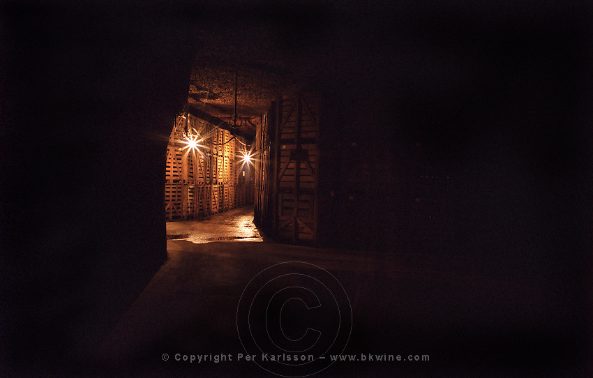 An underground wine cellar with dark corridors and some bright lamps and big wooden cases of bottles for aging at the winery of Gratien et Meyer in Saumur, one of the biggest Loire sparkling wine producers, Maine et Loire, France