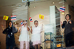 Apr. 19 2010 - BANGKOK, THAILAND: Workers in a department store wave the Thai flag and the flag of the Thai King (yellow flag) as Thai soldiers move into the Silom financial district Monday. Hundreds of Thai soldiers, including reservists and front line units, and riot police moved into the Silom financial district Monday, not far from the red-shirts' main protest rally site, in Ratchaprasong. The heavy show of force is to prevent the Red Shirts from entering the Silom area. Many of soldiers were greeted as heros by workers in the area, who oppose the Red Shirts.   Photo by Jack Kurtz
