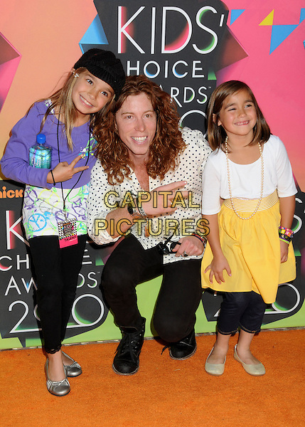 SHAUN WHITE & guests .at the 23rd Annual Nickelodeon Kids' Choice Awards 2010 held at Pauley Pavilion in Westwood, California, USA, March 27th 2010 .arrivals kids full length children girls black boots trousers  white and black polka dot shirt  blue bending down v hand peace sign gesture .CAP/ADM/BP.©Byron Purvis/Admedia/Capital Pictures