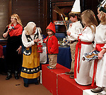 "Washington, CT- 29 December 2013-122913CM16  CL ONLY PLEASE---- Carol Elizabeth Skog, local author of  Enchantment Ädventyr, H.C.A. and I Understand helps Darya Abraham, 2, of Washington who played ""Tomte"" with a lantern, as other children who dressed up for a miniature procession of Sankta Lucia look on, inside the Gunn Memorial Library in Washington on Sunday.   Christopher Massa Republican-American"
