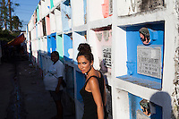 UK celebrity Myleene Klass walks through tomb aisles with Rose Marie Ferrer, 33, to her house where she lives with her large family over children's graves in an inhabited cemetery in Paranaque City, Metro Manila, The Philippines on 18 January 2013. Rose owns a shop in the cemetery where she sells funeral items. She supports her family with this, has breastfed all her 5 children, and is 9 months pregnant now. Photo by Suzanne Lee for Save the Children UK