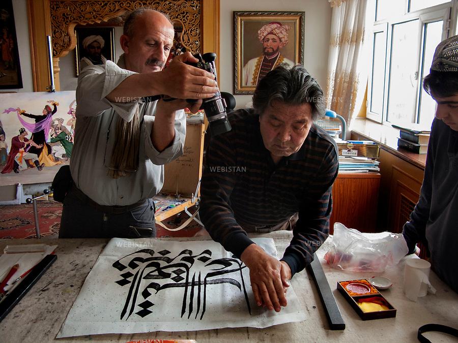 Chine, Turkestan oriental. 2008<br /> Ghazi, peintre et calligraphe, est un artiste r&eacute;put&eacute; dont l&rsquo;oeuvre r&eacute;pand dans le monde la culture du peuple ou&iuml;gour. Travail attentif sous l'oeil de Delazad Deghati et l'objectif du photographe Reza.&nbsp;<br /> Les Ou&iuml;ghours sont un peuple turcophone et musulman sunnite habitant la r&eacute;gion autonome ou&iuml;ghoure du Xinjiang (ancien Turkestan oriental) en Asie centrale. Ils repr&eacute;sentent une des cinquante-six nationalit&eacute;s reconnues officiellement par la r&eacute;publique populaire de Chine. <br /> Photographie prise dans le cadre du voyage initiative de Reza et son fils Delazad, partis tous les deux de Beijing &agrave; Paris pour 16000 kilom&egrave;tres d'aventures. Leurs t&eacute;moignages &eacute;crits et ceux de Rachel Deghati a donn&eacute; lieu &agrave; la publication de l'ouvrage Chemins Parall&egrave;les, en 2009, aux Editions Hoebeke. <br /> <br /> China, East Turkistan. 2008<br /> Ghazi, a painter and calligrapher, is a renowned artist whose work enables the culture of the Uighur people to be spread throughout the world. Careful work under the eye of Delazad Deghati and the objective of the photographer Reza.<br /> The Uighurs are a Turkish-speaking Sunni Muslim people living in the Uyghur Autonomous Region of Xinjiang (former East Turkestan) in Central Asia. They represent one of the fifty-six nationalities officially recognized by the People's Republic of China. <br /> Photography taken during the initiatory travel Reza made with his son Delazad, traveling 16000 kilometers from Beijing to Paris. Their written testimonies and the texts written by Rachel Deghati were collected in a book entitled &quot;Chemins Parall&egrave;les&quot;, published in 2009 by Hoebeke editions.