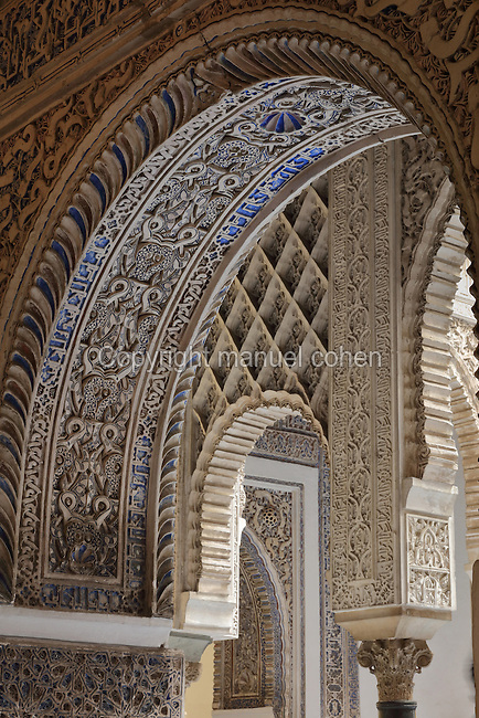 Arch and decorative plasterwork, in the Patio de las Doncellas, or Courtyard of the Maidens, in the Mudejar Palace, or Palacio del Rey Don Pedro, built by Pedro I of Castile, 1334-1369, in 1364, in the Real Alcazar, a Moorish royal palace in Seville, Andalusia, Spain. The Patio de las Doncellas is a courtyard surrounded by muqarnas arches and a central sunken garden. It is the main courtyard of the palace and was named after the Moorish annual tradition of demanding 100 virgins from their Christian kingdoms. The ground floor is in typical Mudejar style but the upper floor was added 1540-72 and shows Renaissance influences. The Alcazar was first founded as a fort in 913, then developed as a palace in the 11th, 12th and 13th centuries and used by both Muslim and Christian rulers. The Alcazar is listed as a UNESCO World Heritage Site. Picture by Manuel Cohen