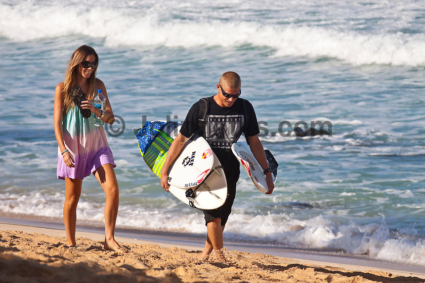 PIPELINE, Oahu/Hawaii (Friday, December 11, 2009) World Title contenders Mick Fanning (AUS) with his wife Karrisa on the beach at Pipeline - Round 2 of the Billabong Pipeline Masters, Event No. 10 of 10 on the 2009 ASP World Tour,was completed today in clean four-to-six foot  waves at the Banzai Pipeline...The third and final event in the Vans Triple Crown (an ASP Specialty Series), the Billabong Pipeline Masters plays host to two dramatic story arcs: the showdown for the 2009 ASP World Title and the requalification race for the 2010 ASP Dream Tour. Amidst the world's best surfers exists a spattering of Pipeline specialists, making the competition field particularly challenging to navigate... This event is the last World Championship event of the year and will decide the 2009 World Tilte between Joel Parkinson (AUS) and Mick Fanning (AUS)...The northern hemisphere winter months on the North Shore signal a concentration of surfing activity with some of the best surfers in the world taking advantage of swells originating in the stormy Northern Pacific. Notable North Shore spots include Waimea Bay, Off The Wall, Backdoor, Log Cabins, Rockpiles and Sunset Beach... Ehukai Beach is more  commonly known as Pipeline and is the most notable surfing spot on the North Shore. It is considered a prime spot for competitions due to its close proximity to the beach, giving spectators, judges, and photographers a great view...The North Shore is considered to be one the surfing world's must see locations and every December hosts three competitions, which make up the Triple Crown of Surfing. The three men's competitions are the Reef Hawaiian Pro at Haleiwa, the O'Neill World Cup of Surfing at Sunset Beach, and the Billabong Pipeline Masters. The three women's competitions are the Reef Hawaiian Pro at Haleiwa, the Gidget Pro at Sunset Beach, and the Billabong Pro on the neighboring island of Maui...Photo: Joliphotos.com