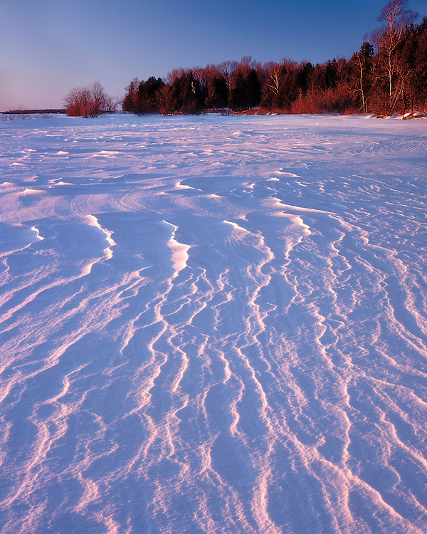 Sunset light on snow patterns on Green Bay; Peninsula State Park, WI