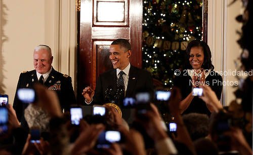 United States President Barack Obama, center, first lady Michelle Obama, right, and Rabbi Larry Bazer, left, arrive for a Hanukkah Reception in the Grand Foyer of the White House  in Washington DC, on December 13, 2012..Credit: Aude Guerrucci / Pool via CNP