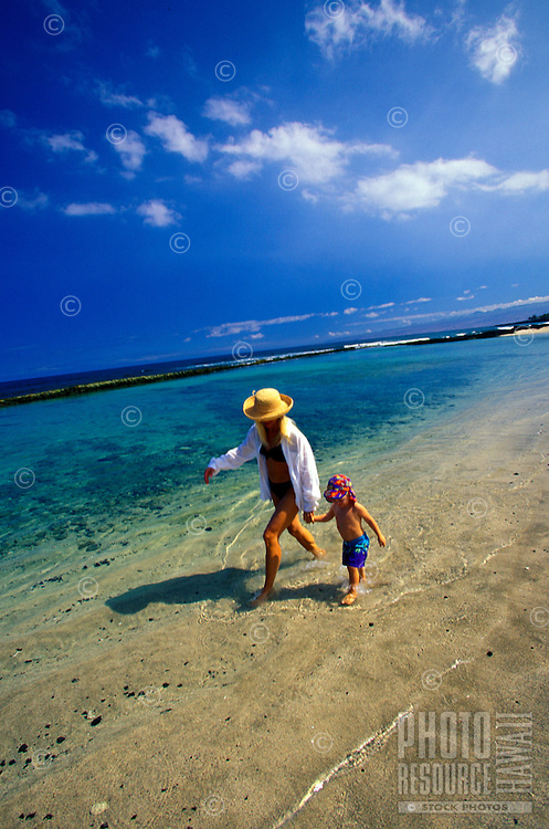 Mother and son in hats walking on the beach on a bright sunny day in Hawaii