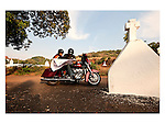 JOURNEYS AND MAPS : Two Harley riders take a break near a village cross near the church to find their way and their location on the India map on their journey in a village in Goa. Photograph © Santosh Verma