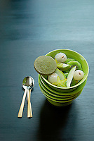 A salad of lychees, kiwi fruit, star fruit and apple in plain green bowls on a black tabletop