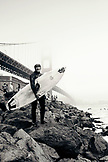 USA, California, San Francisco, portrait of a local surfer at Fort Point beneath the Golden Gate Bridge