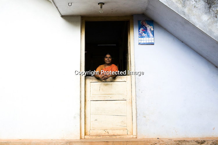 49 years old Joyce took a loan of Rs. 52,000 (1051$) from the bank to build her two room apartment. she pays mortgage of Rs. 500 per month. She lives in her new apartment with her husband and two daughters. She shells raw cashews in cashew processing factory in Prassala, Kanyakumari district in Tamil Nadu, India.. .An estimated number of 500,000 women process cashews for a living in Tamil Nadu and Kerela. 2 million people are employed by cashew industry across India making it the world's biggest exporter of shelled cashews. .The working conditions in these processing units are way below industry standards and violates the basic rights. Wages are as low as Rs. 50 (US $1) per day. The problems for these women is not restricted to low wages. Many women are being injured by their jobs as the factory owners cut corners with health and safety. Oil released during the cashew shelling process is highly caustic, leading to common cases of dermatitis, blistering and discolouration of workers' skin. Women working in these units suffer from pains in their leg muscles, backs and knee joints after squatting positions on mud or concrete floors. It is very rare to find tables and chairs provided on shelling duty..Cashew workers' main concern is to increase their earnings and provide better working conditions. .Photo: Sanjit Das