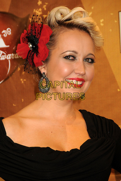 MEGHAN LINSEY of Steel Magnolia.American Country Awards 2010 - Press Room held at the MGM Grand, Las Vegas, California, USA..December 6th, 2010.headshot portrait black red flower in hair smiling lipstick make-up earring .CAP/ADM/BP.©Byron Purvis/AdMedia/Capital Pictures.