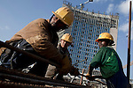 ADDIS ABABA, ETHIOPIA - NOVEMBER 17:  A Chinese construction worker with Ethiopian workers at the new African Union Buildings on November 17, 2010 in Addis Ababa, Ethiopia. The building is built for free. Chinese companies are investing and working all over Africa and in Ethiopia they are mainly occupied with infrastructure projects around the country. Photo by: Per-Anders Pettersson