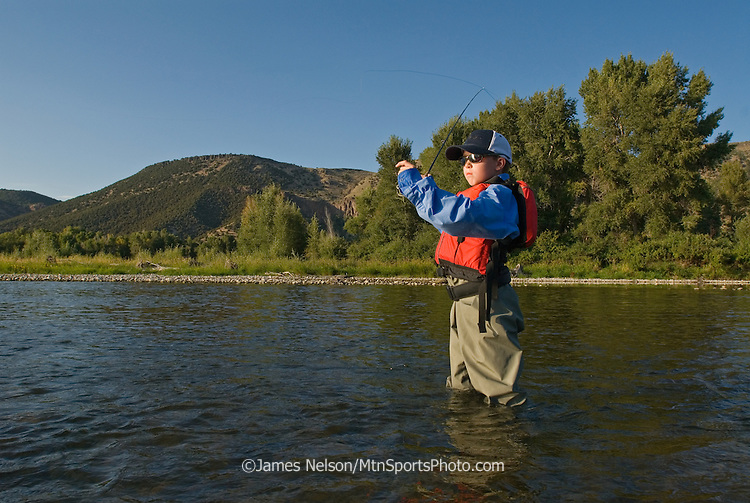 A nine-year-old boy casts a fly for trout on the South Fork of the Snake River, Idaho.