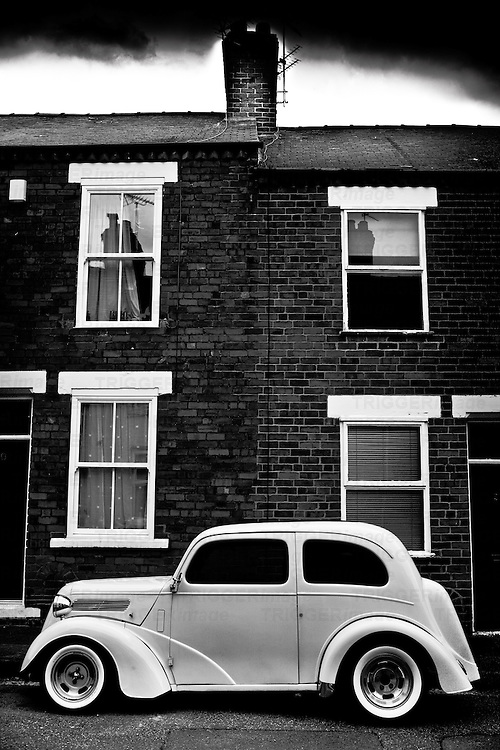 Customised Ford popular car parked in front of a terrace house in York, England.  Afternoon shot stormy sky.