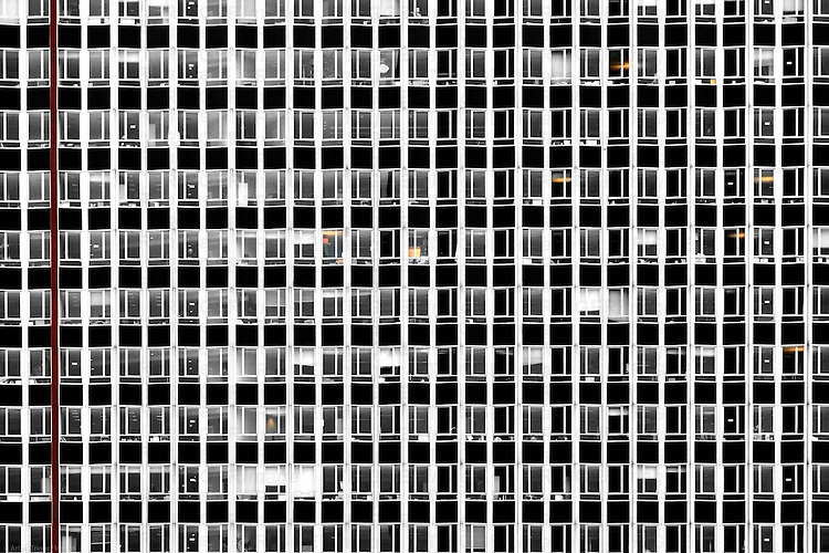 The photograph of the facade of a tall building with many windows.