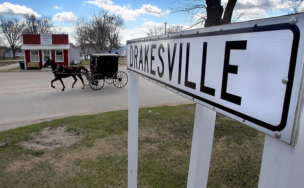 A horse and buggy travels past a business in Drakesville in southeast Iowa's Davis County.   It is among only a handful of rural Iowa counties in the 2010 Census to gain population (2.4 percent).  Much of that population growth is due to a steadily growing Amish population.  (Christopher Gannon/The Des Moines Register)