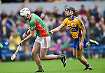 Cillian Duggan of  Clooney-Quin in action against Shane Golden of  Sixmilebridge during their senior county final at Cusack Park. Photograph by John Kelly.