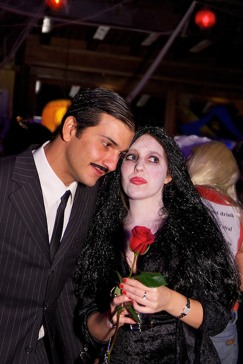 Adams Family couple at a Halloween party.
