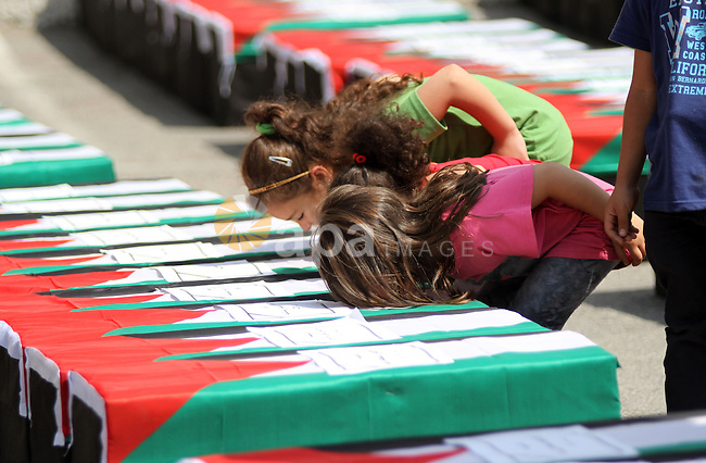 Palestinian girls kiss symbolic coffins during a protest in solidarity with Palestinians killed by Israeli forces in Gaza Strip, in the West Bank City of Ramallah July 22, 2014. A series of Israeli air strikes killed seven people in Gaza, including five members of the same family, an emergency services spokesman said. The deaths hike the total Palestinian toll to 583 since the Israeli military launched Operation Protective Edge on July 8 in a bid to stamp out rocket fire from Gaza. Photo by Shadi Hatem