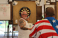 """MEGAN DAVIS/MCDONALD COUNTY PRESS Bob """"T-Bob"""" Kiederer, of Des Moines, Iowa, chats with his teammate as he removes darts from three near-perfect bullseyes. The 2019 Chicken Coop Open was Kiederer's 26th time attending the event. """"I've played with generations of these darters,"""" he said. """"I actually quit my job last year because they wouldn't let me off for the Coop. I have no regrets."""""""