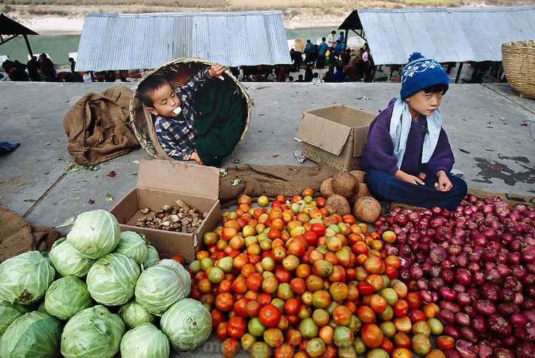 Young market vendors tend their family's cabbage, tomatoes, and onions in the Sunday market in Wangdi Phodrang, Bhutan, a two-hour walk from Shingkhey village. Hungry Planet: What the World Eats (p. 40). This image is featured alongside the Namgay family images in Hungry Planet: What the World Eats.