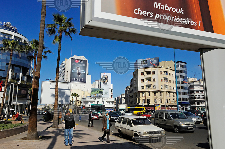 Traffic and pedestrians pass through Casablanca's modern business district. Billboards mounted high on the sides of some of the buildings advertise LG mobile phones, HP computer accessories and Hamilton watches.