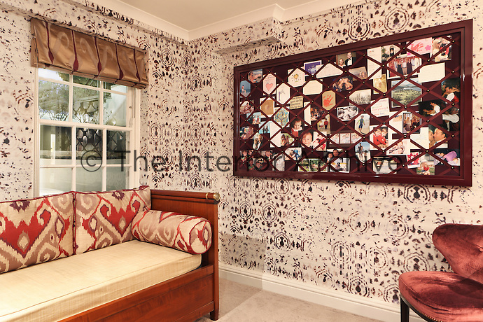 A burgundy pinboard, with an array of family photographs tucked into it, matches the dark red hues of this room