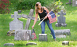 WINSTED CT. 18 May 2018-051818SV06- Georgi Andrews of Winsted replaces old American Flags with new one at a cemetery on Oak Street in Winsted Friday. Andrews and her children help replace the flags at that cemetery every year before Memorial Day.<br /> Steven Valenti Republican-American