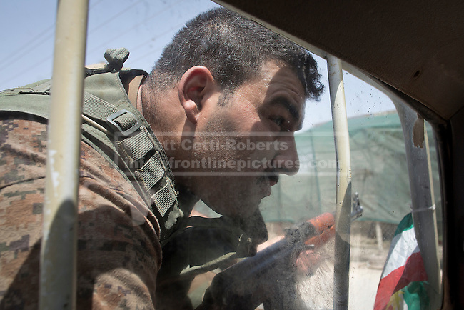 30/06/2014. Khanaqin, Iraq. A Kurdish peshmerga fighter peers to see the road ahead from the back of a peshmerga pick up truck in Jalawla, Iraq. Counted by Kurds as part of their homeland, fighting in the town of Jalawla now consists of occasional skirmishes and exchanges of fire between snipers and heavy machine guns on both sides.<br /> <br /> The peshmerga, roughly translated as those who fight, is at present engaged in fighting ISIS all along the borders of the relatively safe semi-automatous province of Iraqi-Kurdistan. Though a well organised and experienced fighting force they are currently facing ISIS insurgents armed with superior armament taken from the Iraqi Army after they retreated on several fronts. &copy; Matt Cetti-Roberts
