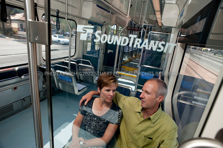 """7/28/2009--Seattle, WA, USA..Kimberly and Tim Abrott of Normandy Park, Wash., take the Sound Transit Link train south out of Seattle towards Tukwila...The Sound Transit Link Light Rail opened in Seattle on July 20th 2009, after decades of planning and political wrangling. Construction of the city's new mass transit system took five years and cost $2.3 billion. By the end of the 2009 Sound Transit says light rail will reach Sea-Tac Airport; the train currently runs 14 miloes from the downtown Westlake station to Tukwila, south of Seattle, with extensions planned to run north and east out of the city.The first efforts to build modern rail transit in the Seattle area began about 50 years ago. A comprehensive plan was defeated by voters three times (1968, 1970, 1995), and then a shortened, """"starter"""" system was passed in 1996. ..©2009 Stuart Isett. All rights reserved."""