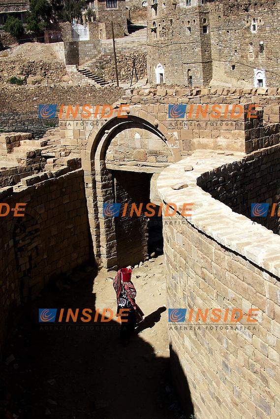 Yemen, Gennaio 2006.A circa 54 chilometri da San'a c'e' una straordinaria antica cittàThilla, questa e' un raro esempio, quasi perfettamente conservato, di città degli altipiani dalle case a torre di pietra. La città, circondata da mura e con le sue vie lastricate, e' costruita interamente con pietre di montagna in modo che ad una certa distanza sia difficile individuarne l'esistenza..Le case pur essendo fatte con lo stesso materiale differiscono le une dalle altre per via dei fregi e delle strutture dei muri..Nella foto:Donna con il burka torna dalla cisterna...A women comes from the cistern in Thilla, this is a little town perfectly conserved no too far from San'a. It is famous for the tower houses made with rocks of the local mountains....Photo Antonietta Baldassarre