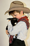 A young cowboy holding a black bunny rabbit tightly