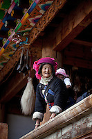 """May 1st, 2011_Shangri-La, Yunnan, China_ Mrs. Kesa Chuoma looks after her grandchildren in their traditional Tibetan farmhouse, in the tiny village of Rime, near the town of Zhongdian (or Shangri-La) in northern Yunnan province, China.  This family is one of several local families taking advantage of """"Home Stays,"""" by opening their homes to visiting tourists.  Photographer: Daniel J. Groshong/The Hummingfish Foundation"""