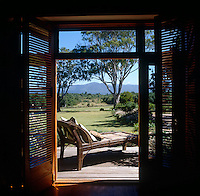 Glimpsed through open double doors the stunning views of the African savannah which can be seen from the sun-deck of a house in Plettenberg Bay