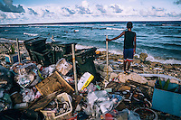 A boy stands on a rock in a rubbish dump and watches his friends play in the water. Although Ebeye's residents make a lot of efforts to keep their island clean, due the luck of regular collections, waste builds up at various dumps across the island.