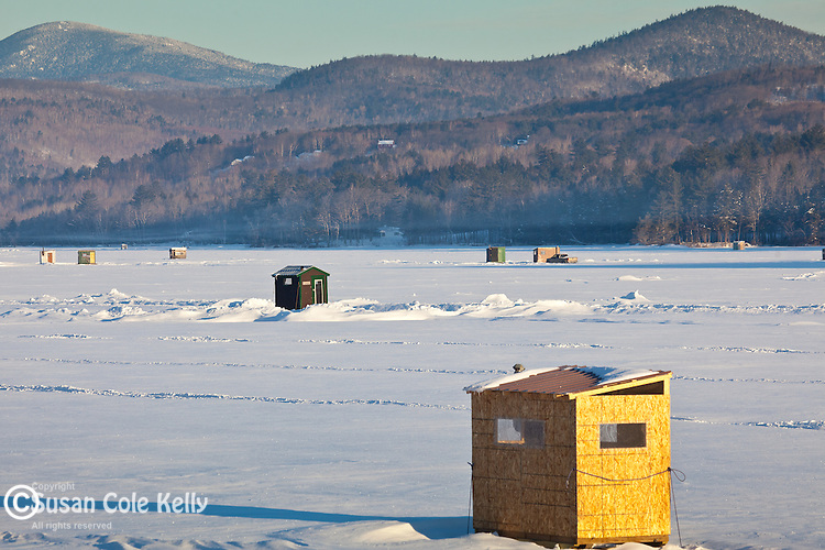 Early morning ice fishing shacks on Wilson Pond in Wilton, ME, USA