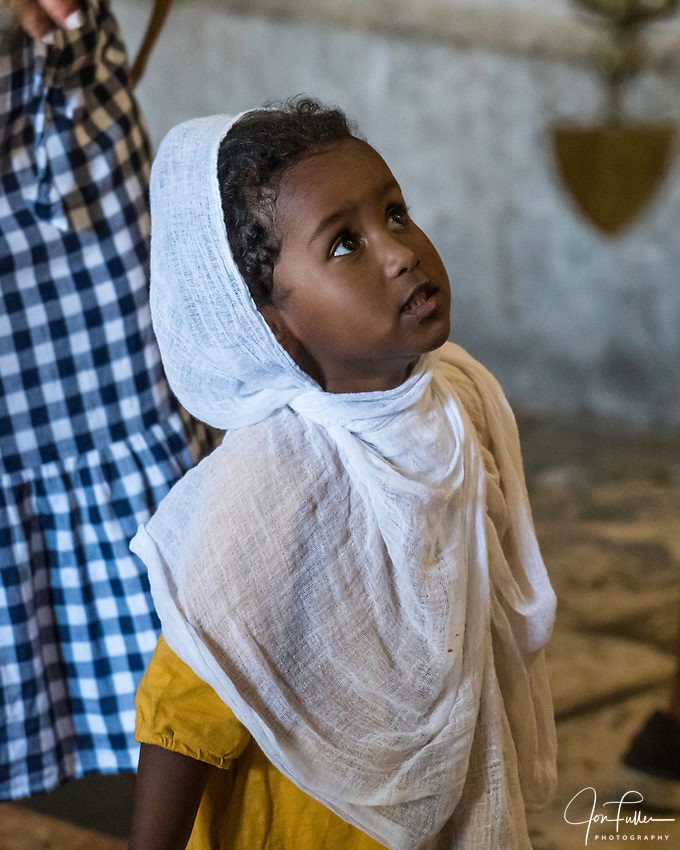A young Ethiopian Christian pilgrim visiting the Church of the Holy Sepulchre in the Christian Quarter of the Old City of Jerusalem.  The Old City of Jerusalem and its Walls is a UNESCO World Heritage Site.  This church was built over the site believed by many to be location of the death and burial of Jesus Christ.