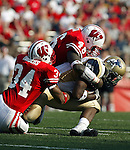 Madison, Wisconsin - 9/6/2003.  University of Wisconsin linebackers Kareem Timbers (38) and Jeff Mack (48) tackle University of Akron wide receiver Nick Sparks (9) during the game at Camp Randall. Wisconsin beat Akron 48-31. (Photo by David Stluka).