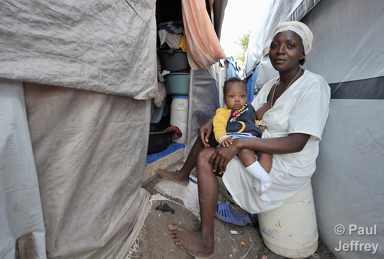 "A mother and her child sit between tents in the largest ""tent city"" of Haitian earthquake survivors, located on a former nine-hole golf course in Port-au-Prince. The Petionville Club is host to more than 44,000 people.."
