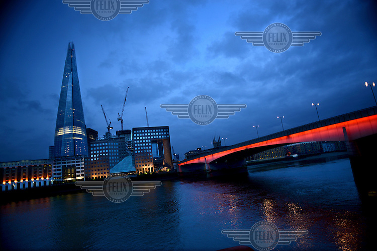 A view from the north side of the River Thames south to London Bridge, illuminated in Red, and the Shard rising 310 metres in the centre.